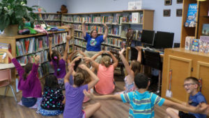 Storytime group at CPL: Ms Shawn Reading and kids standing and doing arm motions