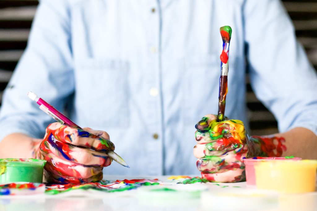 A man wearing a light blue button up shirt sits in the background while holding a paintbrush in one hand and a pencil in the other. His hands and tools are completely messy and covered in paint.