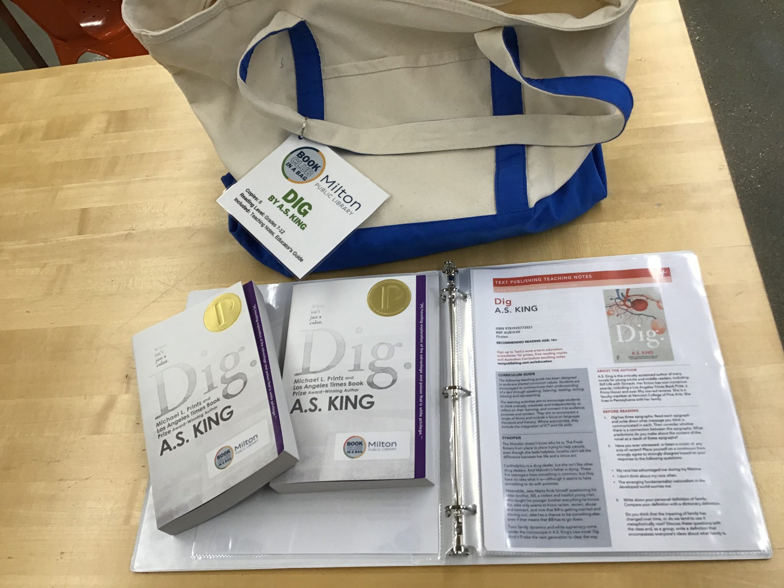 Canvas tote bag with two copies of Dig displayed over the book club kit binder.
