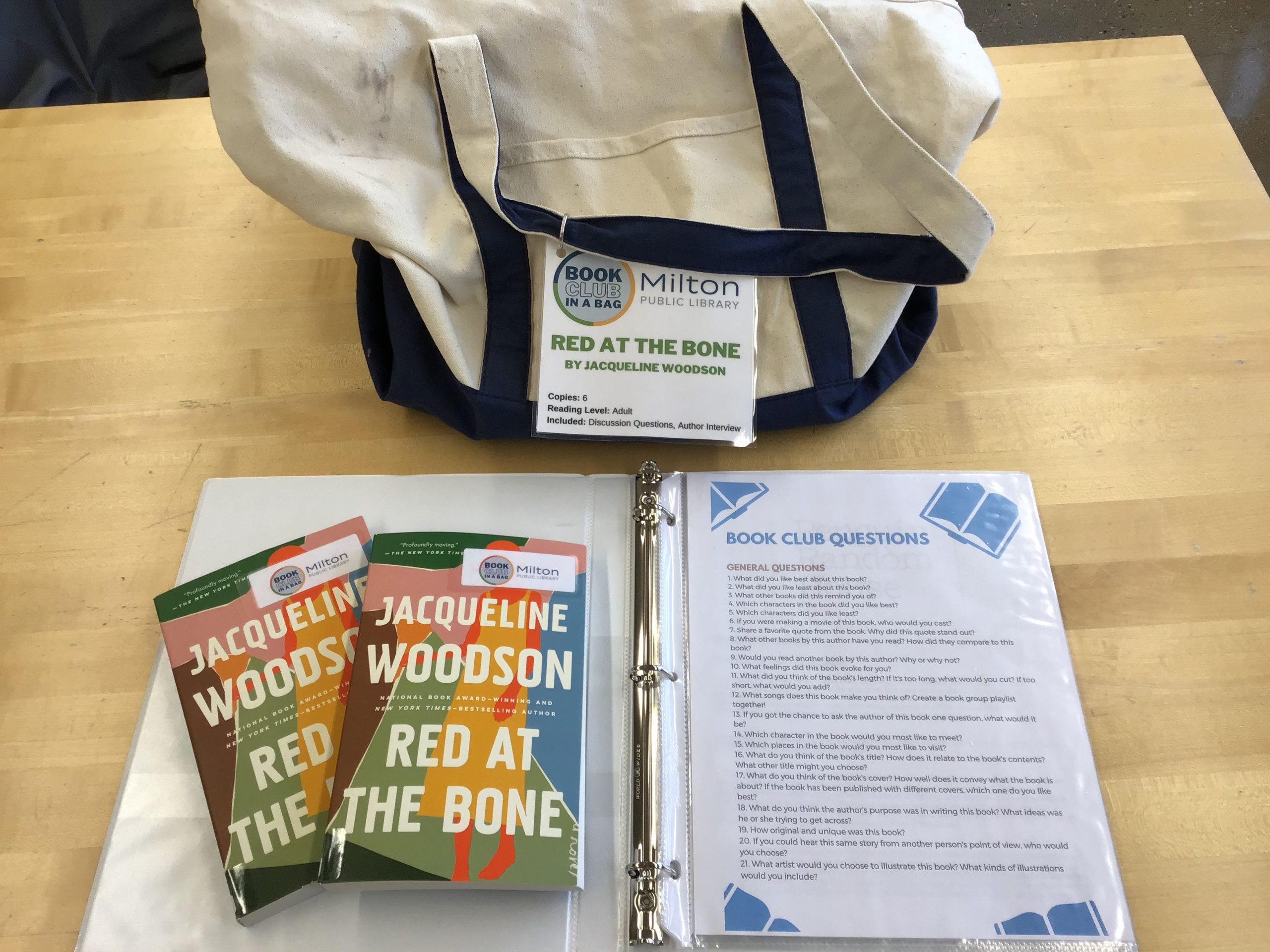 Canvas bag with two copies of Red At the Bone displayed on top of the book club notes.