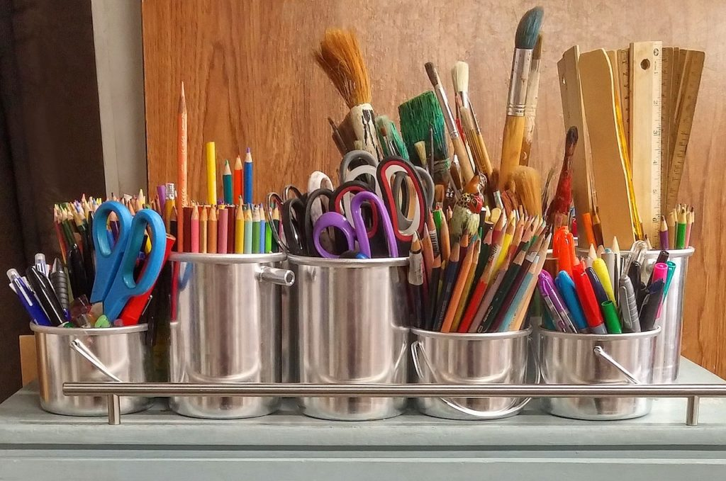 An art caddy with chrome containers full of colored pencils, scissors, rulers, paint brushes, markers and pens.