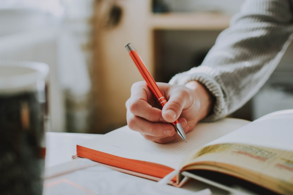Image of someone holding an orange pen hovering over an open journal, ready to write.