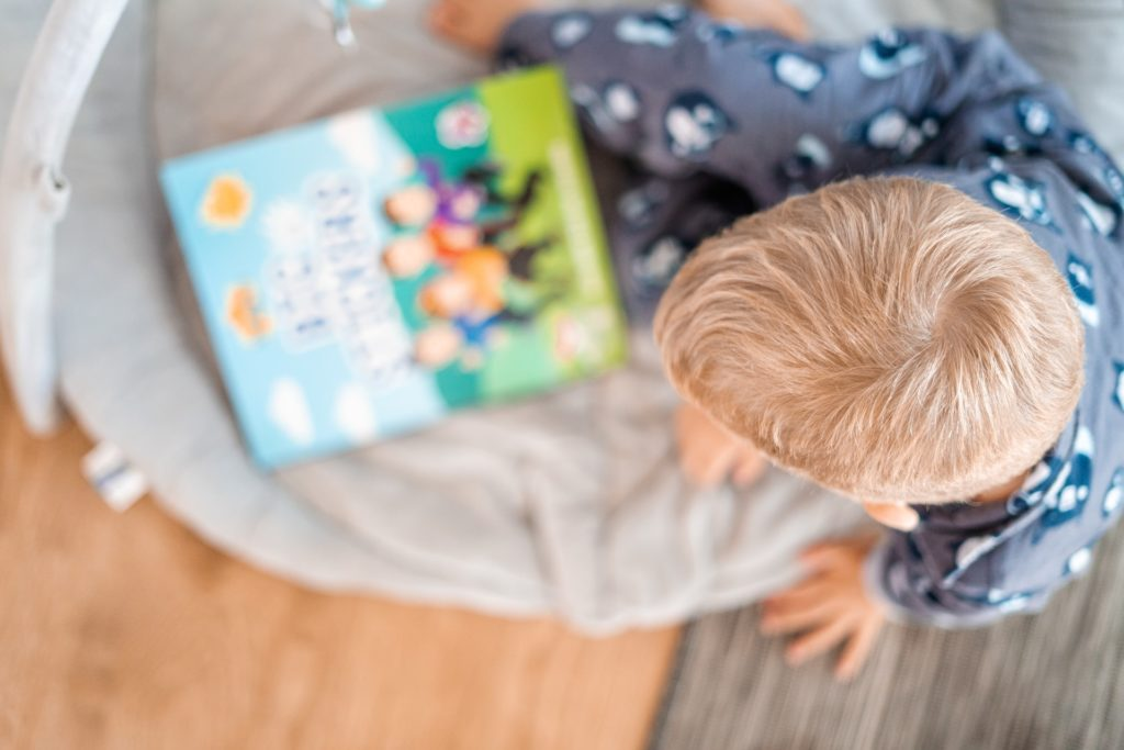 Blurry image looking down on a child in pajamas with a book in his hand.