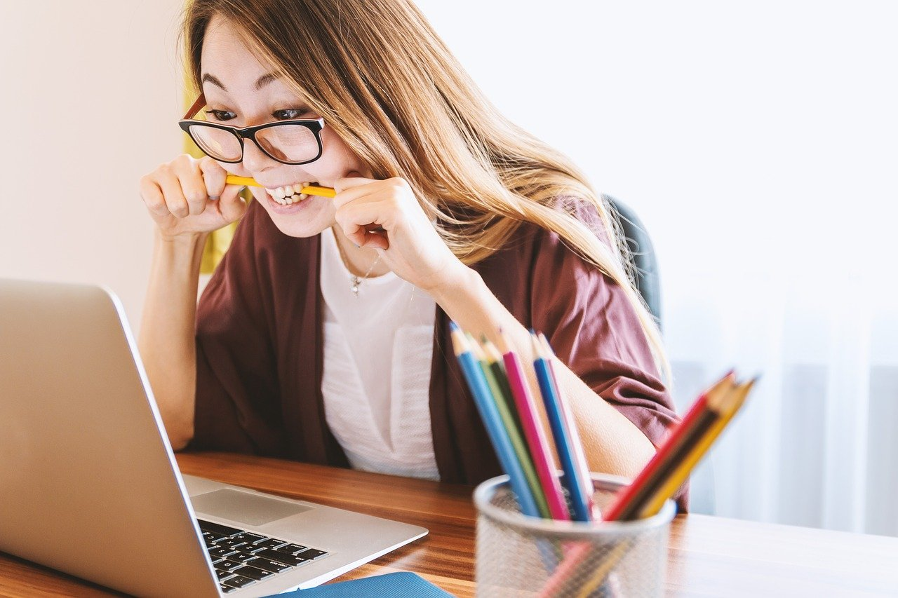 A young lady wearing glasses looking at a laptop while biting a pencil between her teeth in what looks like anxiety.