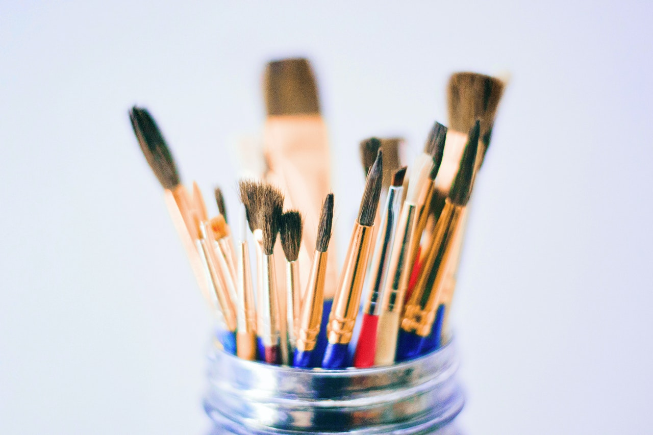 An up-close image of various sizes of paint brushes inside of a mason jar.