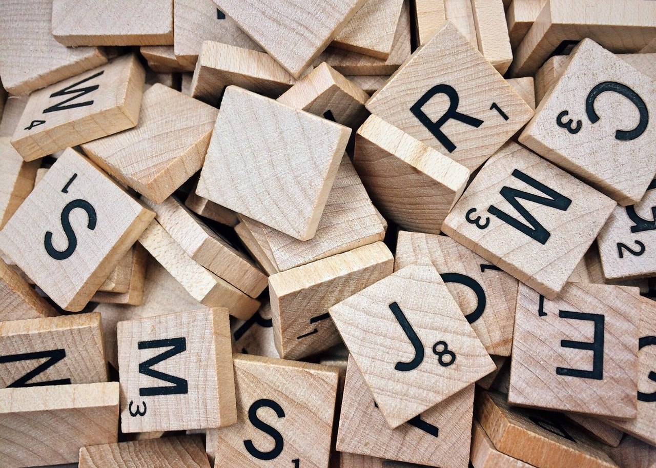 A close up picture of a pile of Scrabble letter game pieces.