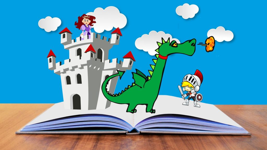 Book laying on table open to the middle. A princess in a castle, a dragon breathing fire, and a knight are all standing on top of the book pages.