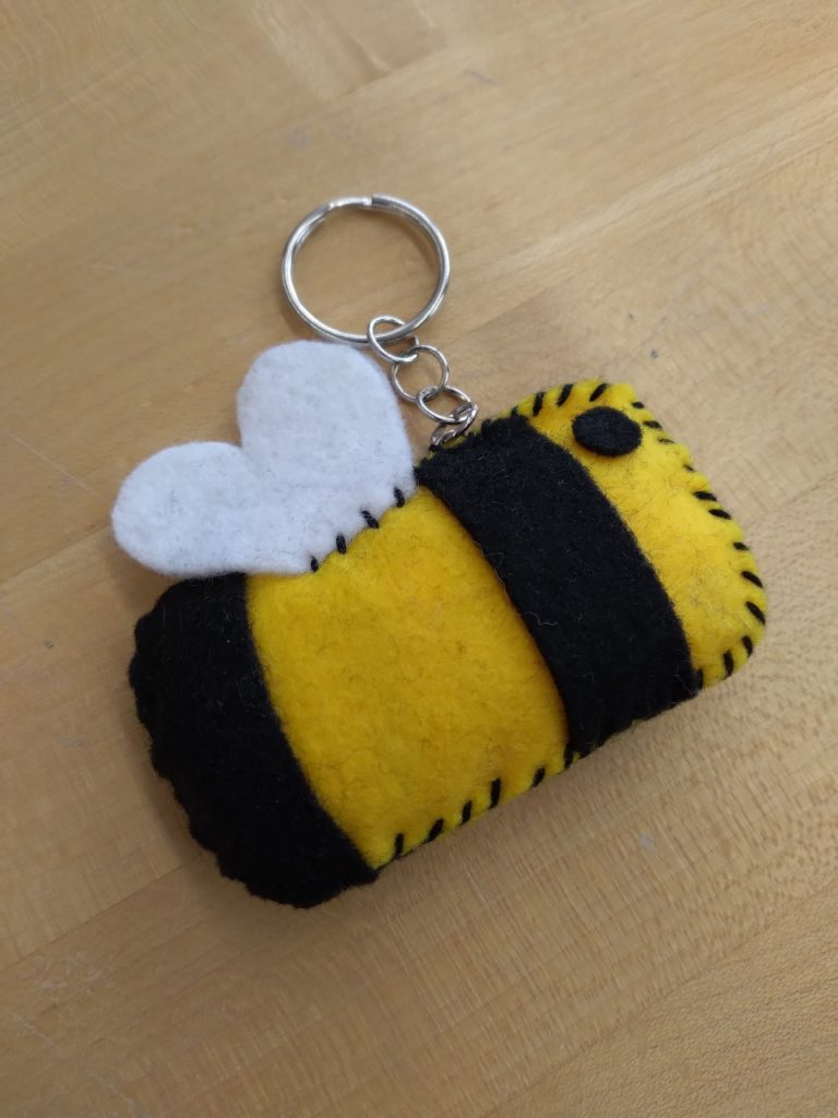 A felt made black and yellow bee with white felt wings stuffed and stitched with black string. It is attached to a key ring and chain.