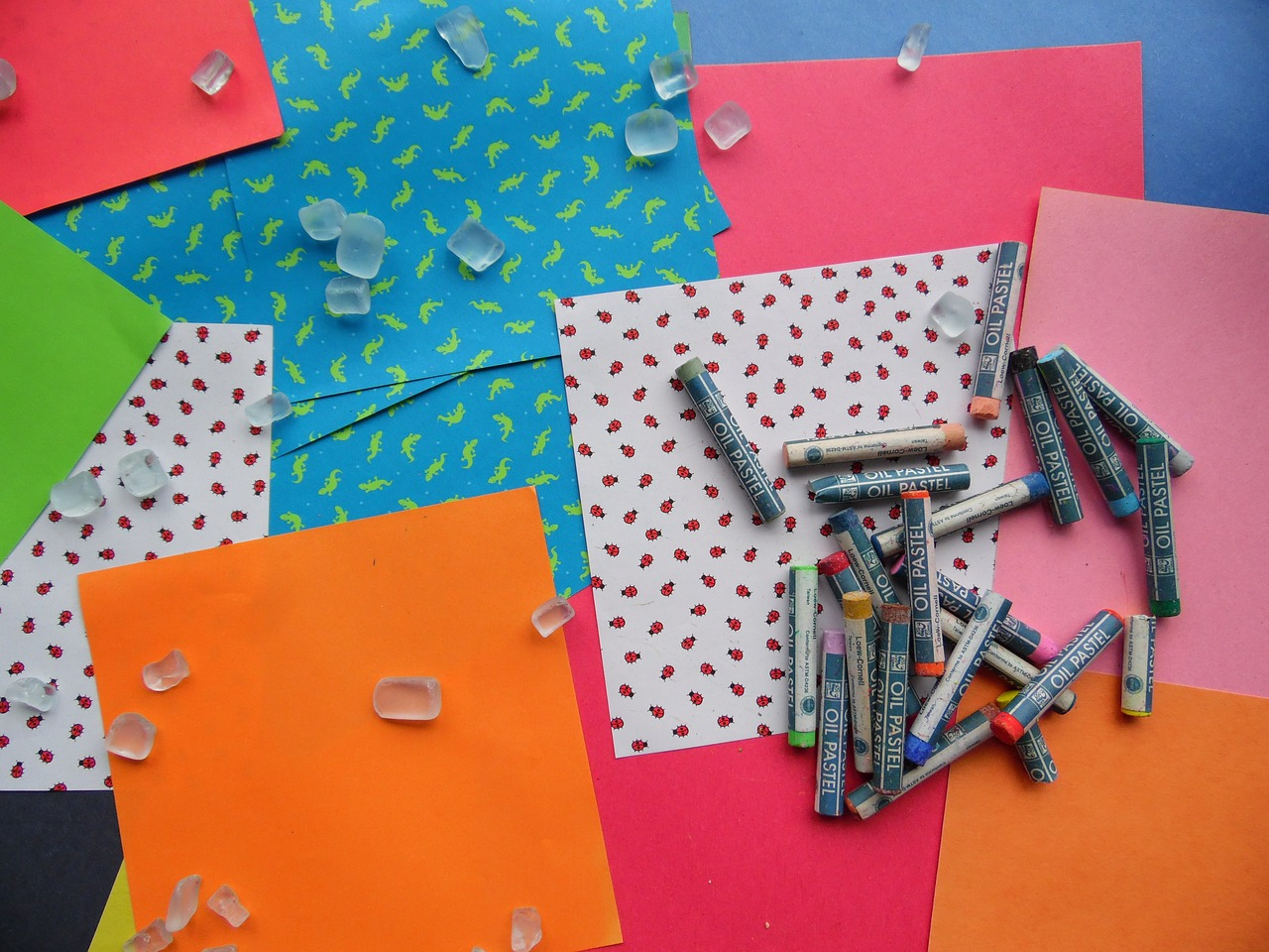 Multi-colored craft paper scattered with oil pastels and craft pieces sprinkled on top.