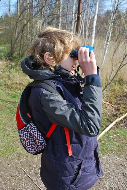 Tween boy looking through binoculars outside.