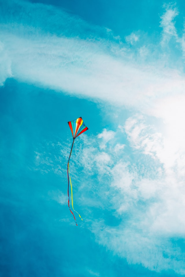A colorful kite high in the blue sky.