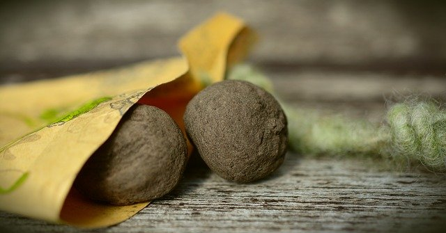 Two seed bombs on a wooden table.