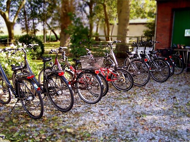 A row of different kinds of bicycles parked outside.