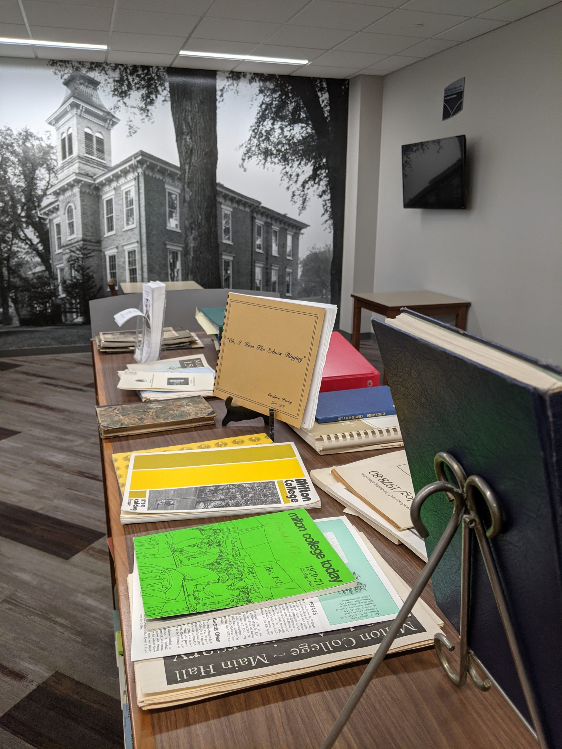 Image of various Milton College paraphenalia displayed atop a book shelf with a mural image of an old campus building.