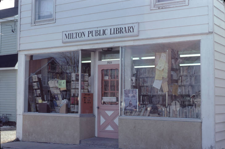 Picture of old library location on West side of town. White building front with large windows and a sign that reads Milton Public Library