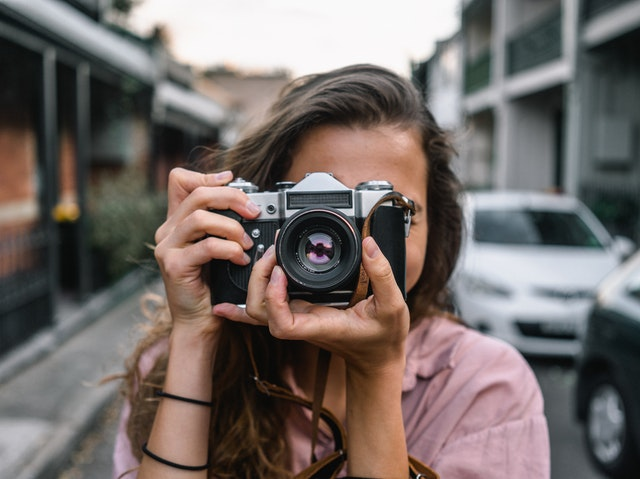 Young woman holding a camera over her face taking a picture