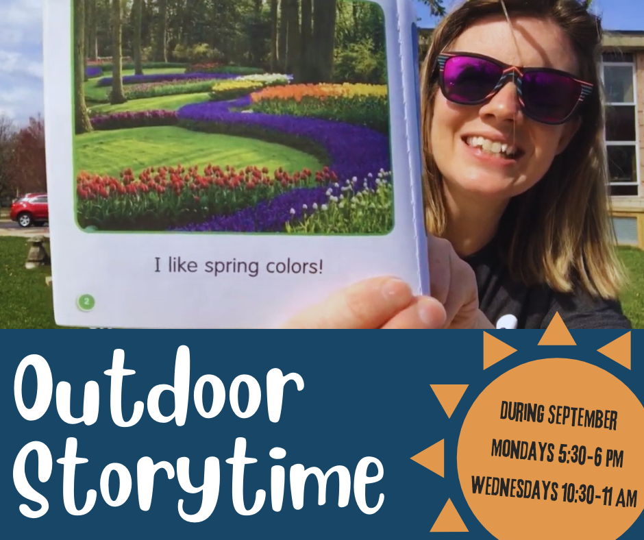 A picture of Jayme holding up a book, reading outdoors.
