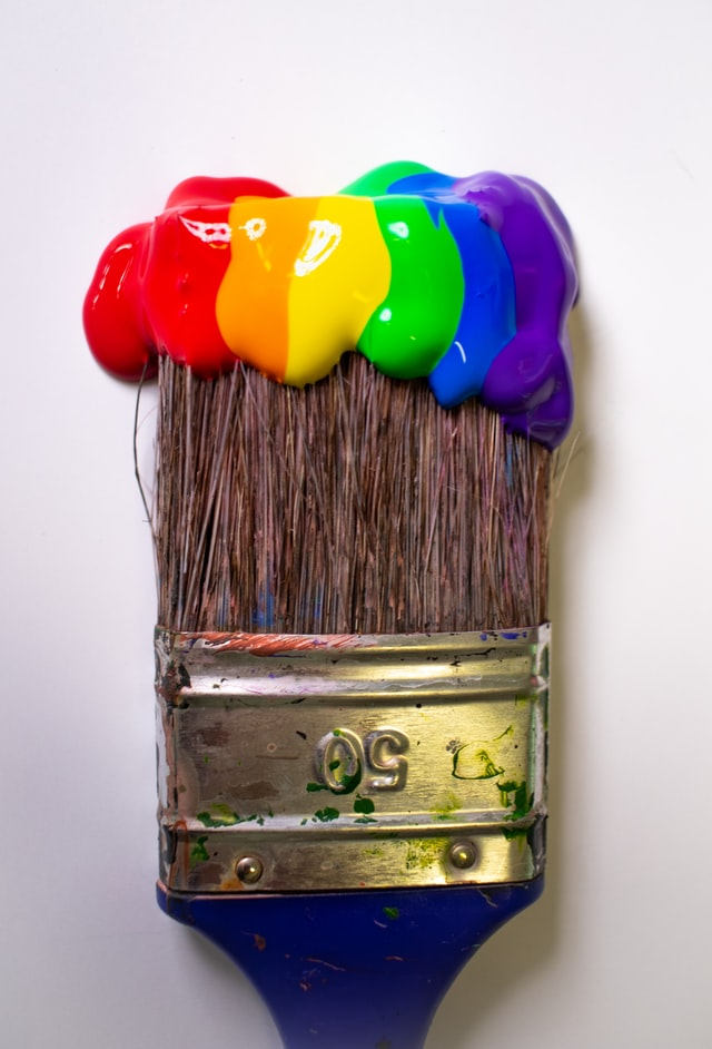 Large paintbrush with a rainbow color of paints on it.