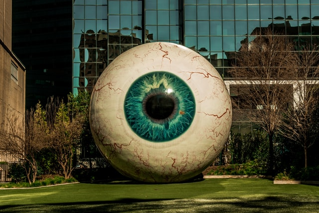 Large, blue eyeball in front lawn of building.