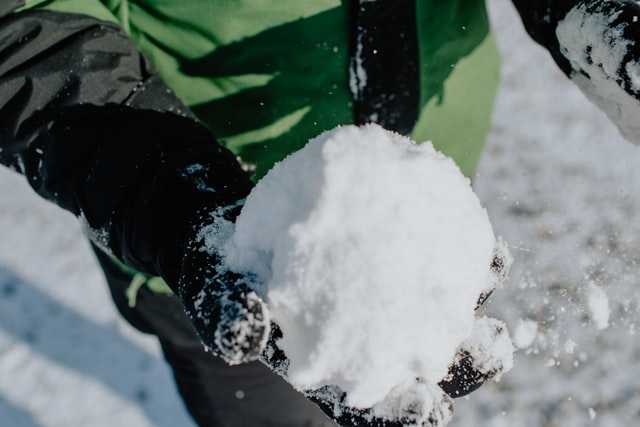 A child's gloved hand holding a white snowball.