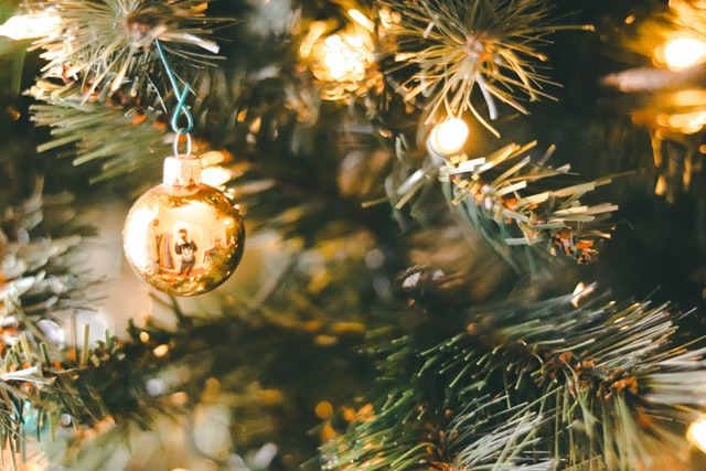 A gold ball ornament handing from a light Christmas tree.