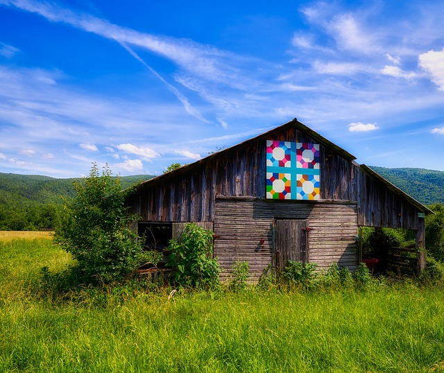 Old barn with a colorful wooden barn quilt hanging on top.