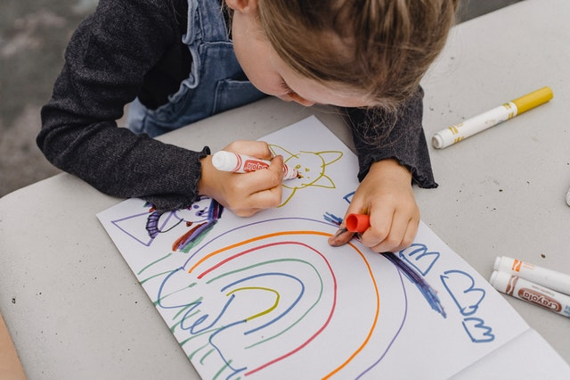 A child using colorful markers to draw a rainbow.