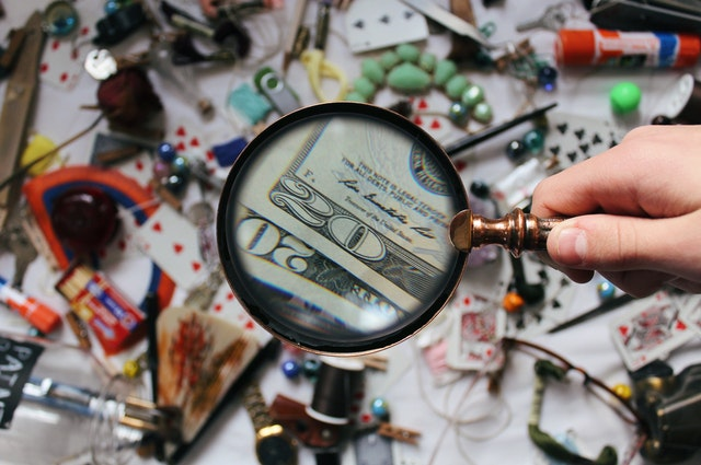 Hand holding a magnifying glass over a mish mash of things.